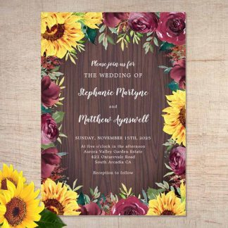 Sunflower wedding invitations with burgundy roses and wood background.